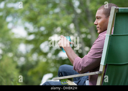 A man seated in a chair in a garden, relaxing. - Stock Photo