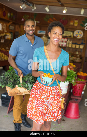 Two people in a farm shop, choosing organic vegetables. - Stock Photo