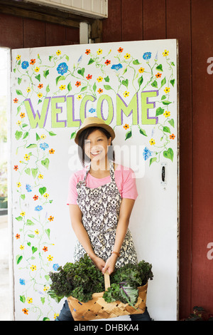 Working on an organic farm. A young Asian woman by the Welcome sign with a large basket of vegetables, freshly picked. - Stock Photo
