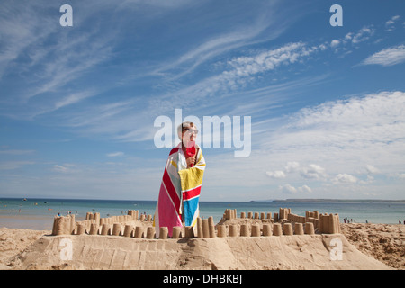 A boy standing beside a sandcastle, on top of a mound of sand. Beach. - Stock Photo