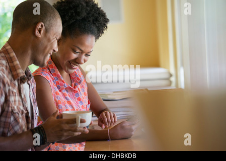 Two people using a digital tablet, seated close together at a cafe. Coffee cups. - Stock Photo