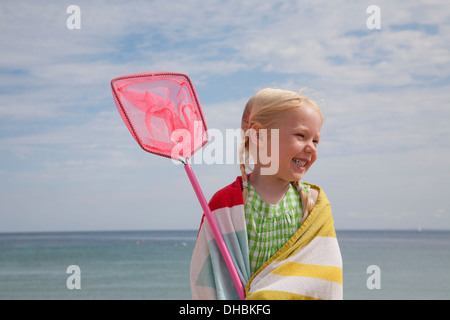 A young girl with a beach towel around her shoulders, carrying a small fishing net. - Stock Photo