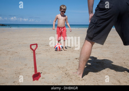 A boy playing football with a man on the sand. Father and son. A beach spade upright in the sand. - Stock Photo