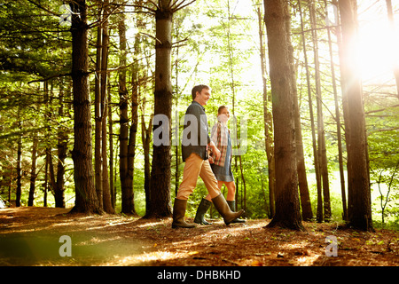 Three people, a family walking in woodland in the late afternoon. - Stock Photo