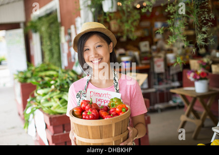 A woman working on an organic farm stand, displaying fresh vegetables for sale. - Stock Photo