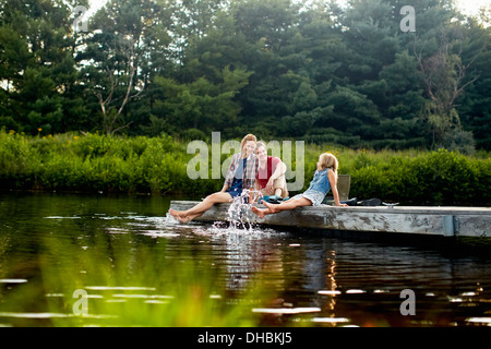 Three people, two adults and a child relaxing on a jetty, with their feet in the water at the end of a day. - Stock Photo