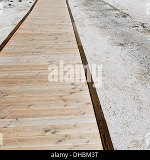 A boardwalk extending across the Midway Geyser in Yellowstone National Park. - Stock Photo