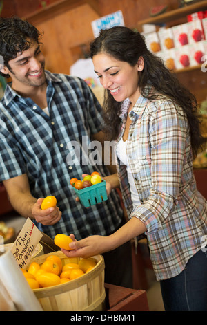 A farm growing and selling organic vegetables and fruit. A man and woman working together. - Stock Photo