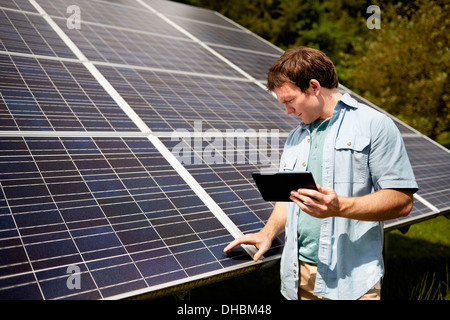 A farmer closely inspecting the surface of a solar panel on the farm. - Stock Photo