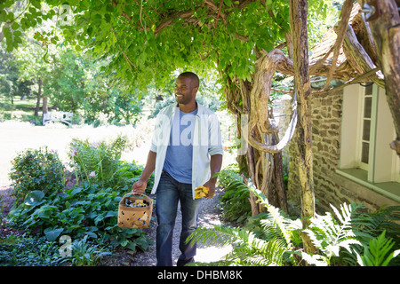 A farm growing and selling organic vegetables and fruit. A man working. - Stock Photo