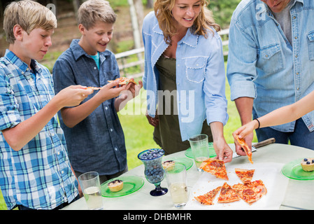 Organic Farm. An outdoor family party and picnic. Adults and children. Plate of pizza. - Stock Photo