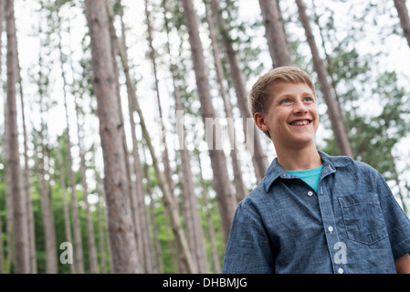 A boy standing among trees on the shore of a lake. - Stock Photo