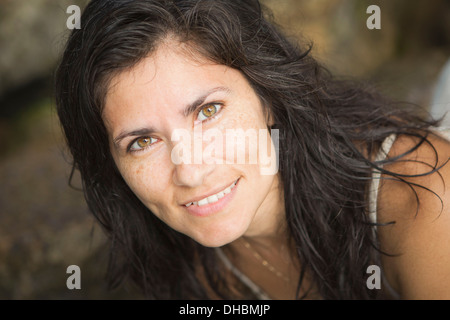 Close up of a smiling woman with freckles on her face. - Stock Photo