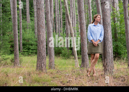 A woman standing among the trees on the shore of a lake in New York state. - Stock Photo