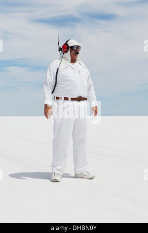 A man in white overalls, with a radio headset, a race official timekeeper at a car racing event, Speed Week. - Stock Photo