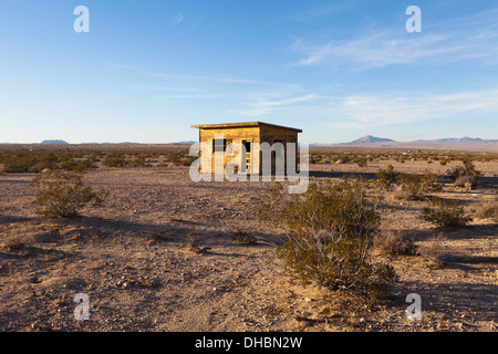 A small abandoned building in the Mojave desert landscape. - Stock Photo
