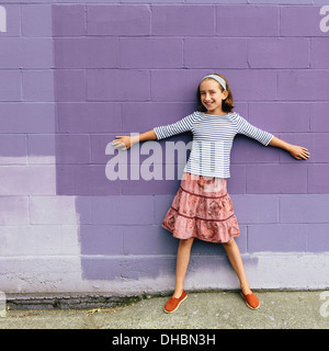 A ten year old girl in a tiered skirt, standing with her arms outstretched, leaning against a wall. - Stock Photo