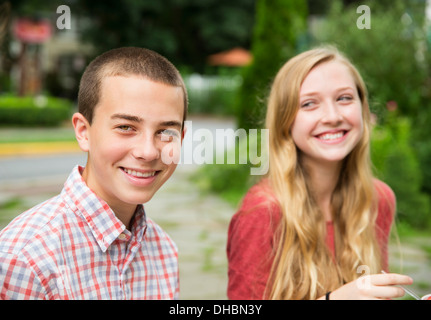 Two young people, boy and girl sitting side by side laughing. - Stock Photo