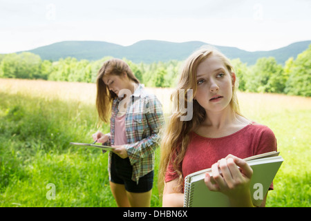 Two young girls sitting outside on the grass, with sketch pads and pencils. - Stock Photo