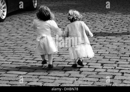 2 little Girls dressed up participating in a wedding, decide to run towards the Park to play instead. - Stock Photo