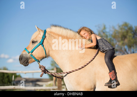 A young girl sitting on a horse. - Stock Photo