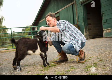 An organic farm in the Catskills. A man with a small black goat. - Stock Photo