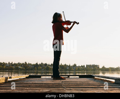 A ten year old girl playing the violin at dawn on a wooden dock. - Stock Photo