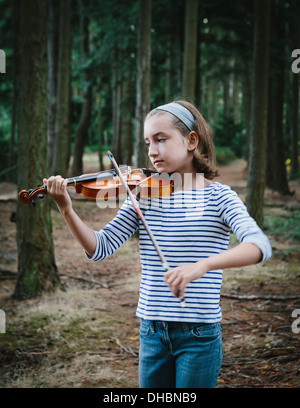 A ten year old girl playing the violin in Discovery Park, Seattle. - Stock Photo