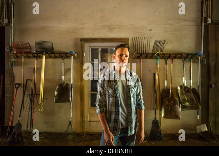 An organic farm in the Catskills. A man standing in a barn with equipment stored around the walls. - Stock Photo