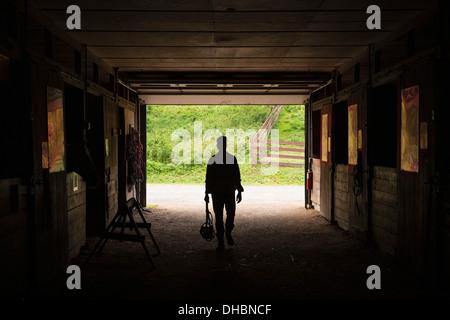 An organic farm in the Catskills. A man walking through a stable. - Stock Photo