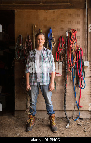 An organic farm in the Catskills. A man standing in a tack room in a stable. - Stock Photo