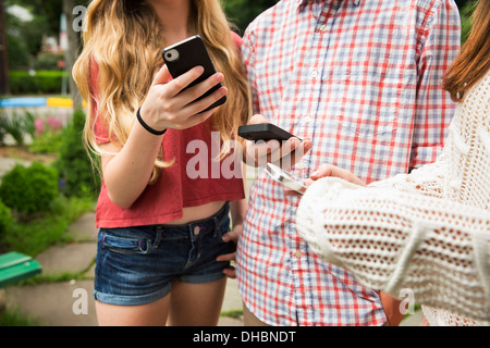 Two friends, a boy and girl looking at their phones. - Stock Photo