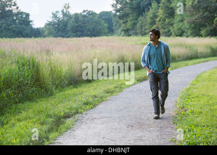 A young man walking down a path with his hands in his pockets. - Stock Photo