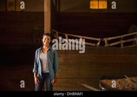 An organic farm in the Catskills.  A woman in a horse stable. - Stock Photo