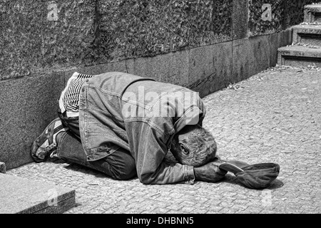 One of the many homeless in Prague, Europe lying on the street next to the river, begging tourists for money. - Stock Photo