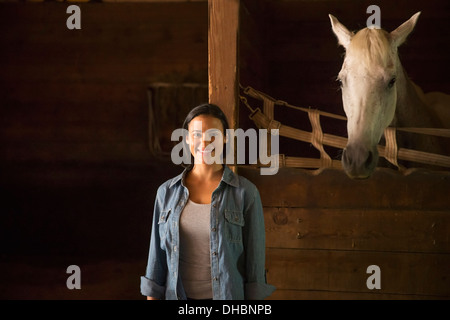 An organic farm in the Catskills. A woman standing in a stable, with a white horse looking over the stall. - Stock Photo