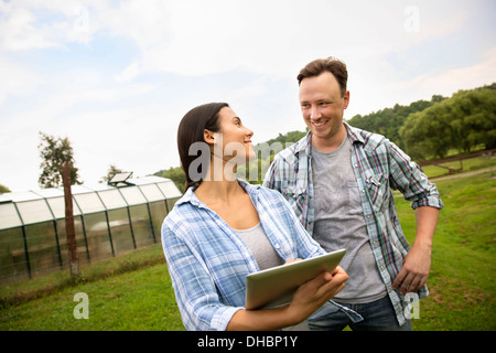 An organic farm in the Catskills. Two people using a digital tablet outdoors. - Stock Photo