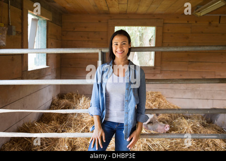An organic farm in the Catskills. A woman beside a pig in a pen, standing in deep straw. - Stock Photo