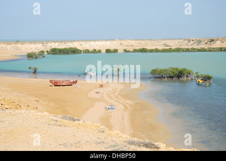 A landscape of Taroa beach with fishing boats on the lagoon with turquoise water and a golden sandy beach in Colombia - Stock Photo