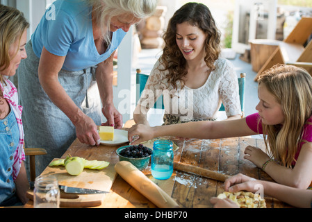 Farmhouse in the country in New York State. Four generations of women in a family baking cookies and apple pie. - Stock Photo