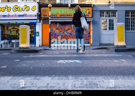 A women crosses a Pelican Crossing on the Caledonian Road in Islington North London. - Stock Photo
