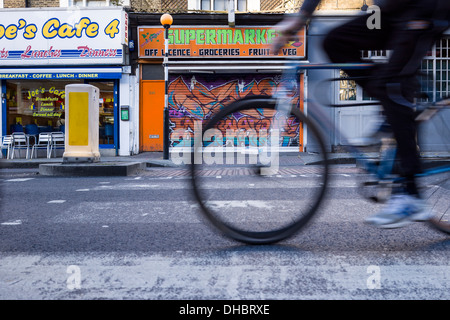 A pedal cyclist crosses a Pelican Crossing on the Caledonian Road in Islington North London. - Stock Photo