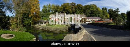 A panorama of iconic Swan Hotel by the roadbridge over the River Coln in Bibury, Gloucestershire, UK - Stock Photo