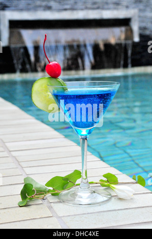 A glass of blue cocktail drink by the pool - Stock Photo