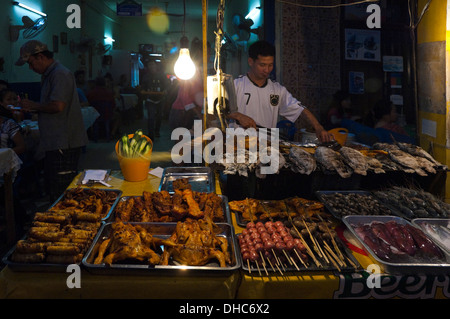 Horizontal portrait of a local Lao man barbecuing whole fish on a grill at a streetside cafe at night. - Stock Photo