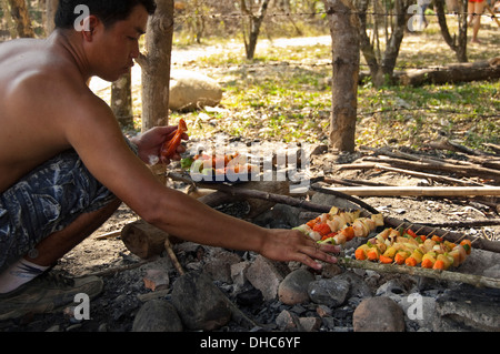 Horizontal portrait of a local Lao man barbecing kebabs in the countryside on a sunny day. - Stock Photo