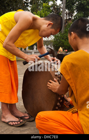 Vertical portrait of young Buddhist monks mending a ceremonial drum at their temple in Luang Prabang. - Stock Photo