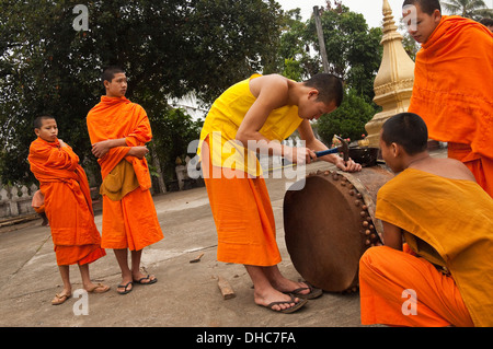 Horizontal portrait of young Buddhist monks mending a ceremonial drum at their temple in Luang Prabang. - Stock Photo