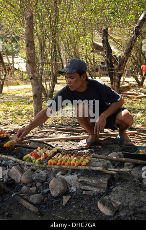 Vertical portrait of a local Lao man barbecing kebabs in the countryside on a sunny day. - Stock Photo