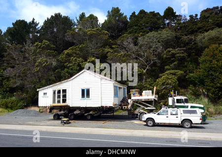 Transporting an old house to a new location in New Zealand - Stock Photo
